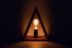 Classic Edison old glowing light bulb with filament in loft lamp standing in wooden triangl as a candle. Abstract Stock Photo
