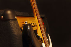 Classic electric guitar with combo amplifier on black background. Shallow depth of field, low key, close up. Stock Photos