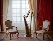 Classic elegant chairs and harp. Two classic chairs and a harp in very elegant setting, window and red and white curtains Royalty Free Stock Photo