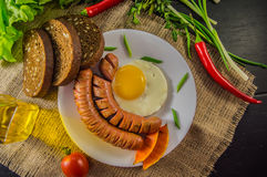 The classic English breakfast with scrambled eggs and sausages. Top view. Black background of wood. Close-up Stock Photography