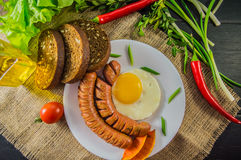The classic English breakfast with scrambled eggs and sausages. Top view. Black background of wood. Close-up Royalty Free Stock Photos