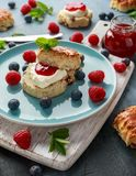 Classic English scones with clotted cream, strawberries jam and other fruit stock image