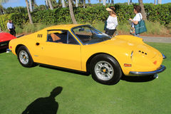 Classic Ferrari sports car lineup side view. Classic yellow dino 246 gt by Ferrari in a lineup and two lady onlookers. focus on front end and fender stock images