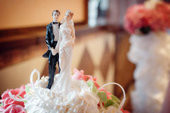 Classic figurines on a wedding cake the newlyweds. White Stock Photography