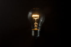 Classic filament bulb. On a dark background both on and off. No wiring Stock Images
