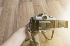 A classic film camera on the back panel showing film compartment and view finder with wooden floor background. A man holding a classic film camera on the back royalty free stock images