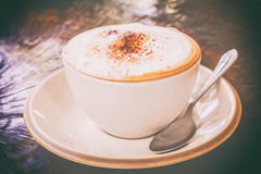 Classic foamy cappuccino in on a dark grained wood table. Royalty Free Stock Photography