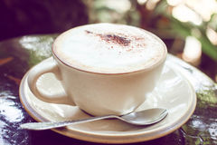 Classic foamy cappuccino in on a dark grained wood table. Royalty Free Stock Images