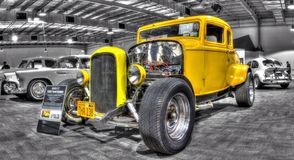 Classic 1932 Ford Coupe hot rod. Classic American 1930s yellow Ford Coupe hot rod on display at the 2016 Meguiar's Motorex in Melbourne, Australia on a black and Stock Photos