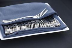 Classic forks covered with a blue napkin over a plate Stock Images