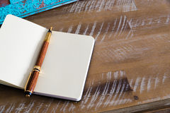Classic fountain pen and open notebook on wooden table Stock Photo