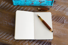 Classic fountain pen and open notebook on wooden table Stock Image