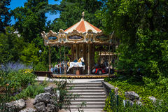 Classic french carousel in a green park. Royalty Free Stock Photo