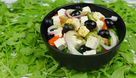 Classic fresh beautiful delicious Greek salad. With olives and feta cheese in a black plate with rucola Royalty Free Stock Photography