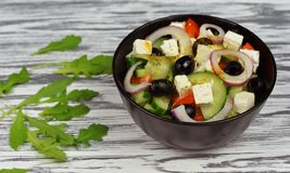 Classic fresh beautiful delicious Greek salad. With olives and feta cheese with fresh rucola on a wooden background Royalty Free Stock Photos