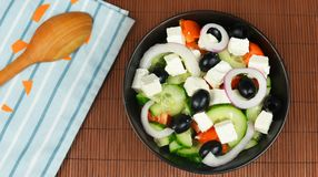 Classic fresh beautiful delicious Greek salad. With olives and feta cheese in a black plate Royalty Free Stock Photography