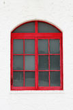 Classic glass red window. On the white wall Stock Photography