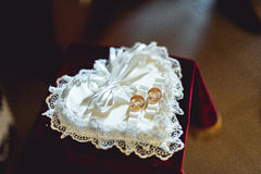 Classic gold wedding ring on small heart looking pillow Stock Photography