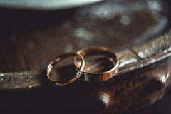 Classic gold wedding rings on the edge of barrel. Classic gold wedding ring on the edge of a wooden barrel. macro royalty free stock images
