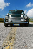 Classic green Mini Cooper. A british green Mini Cooper with white stripes on the roof parked on a road on a sunny day Stock Photos