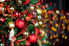 Christmas background with flashing garland on the tree. Classic green new year tree with flashing garland in the dark room. Christmas interior background Royalty Free Stock Photo