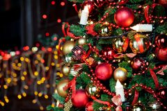 Christmas background with flashing garland on the tree. Classic green new year tree with flashing garland in the dark room. Christmas interior background Stock Photos