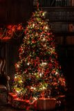 Christmas background with flashing garland on the tree. Classic green new year tree with flashing garland in the dark room. Christmas interior background Stock Image
