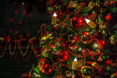 Christmas background with flashing garland on the tree. Classic green new year tree with flashing garland in the dark room. Christmas interior background Stock Photography
