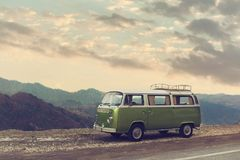 Classic Green Vintage Camper Van Parked on Road. Classic Green Vintage Camper Van Parked on Road under clouds royalty free stock images