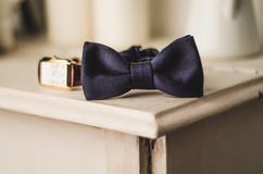 Classic groom accessories: blue bow tie and watch on a wooden table. Set of men's stylish vintage clothing. Male