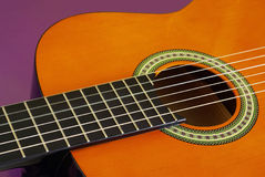Classic Guitar. Closeup detail of a classic guitar over purple background Royalty Free Stock Photo