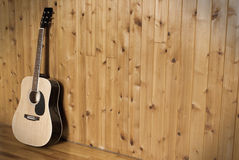 Classic Guitar. A vintage styled image of a classic acoustic guitar leaning on a wooden wall Stock Photo
