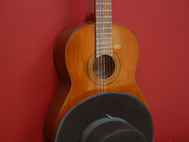 Classic Guitar Displayed with Hat. A Classic Guitar is displayed against a red background with a black, Spanish style hat Royalty Free Stock Photography