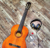 Classic guitar and headphones on a wooden board in hdr Royalty Free Stock Photo