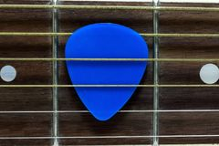 Classic Guitar Neck. A colour image of a 6 string classical guitar neck with a guitar pick in the strings stock photos