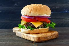 Classic hamburger on a paddle board over dark wood. Classic hamburger with onions, tomato, cheese and lettuce on a paddle board over dark wood stock photos