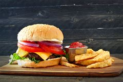 Classic hamburger with potato wedges against dark wood Royalty Free Stock Photo