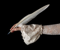 Classic hand writing with goose feather. Female hand in antique sleeve writing with a quill feather Royalty Free Stock Photography