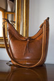 Classic handbag. A classic-brown handbag on a chest of drawers with a mirror behind Stock Photography