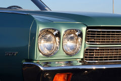 Classic Headlights. The front end of a classic car showing headlights, fender,grill, and windshield royalty free stock images