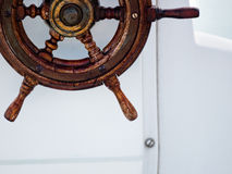 Classic helm wheel. Classic brown wooden halm wheel on a white boat stock photos