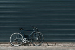Classic hipster bicycle standing near black wall outdoors. Black classic hipster bicycle standing near black wall outdoors royalty free stock photo