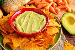 Classic Homemade avocado hummus with olive oil, carrots, pita chips, lime, chilli, parsley. Royalty Free Stock Image