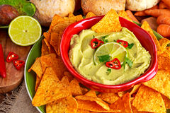 Classic Homemade avocado hummus with olive oil, carrots, pita chips, lime, chilli, parsley. Royalty Free Stock Photography