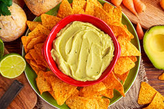 Classic Homemade avocado hummus with olive oil, carrots, pita chips, lime, chilli, parsley. Stock Photography