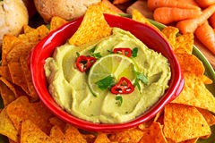 Classic Homemade avocado hummus with olive oil, carrots, pita chips, lime, chilli, parsley. Royalty Free Stock Images