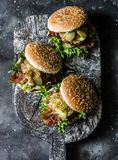 Classic homemade burger with pork cutlet, bacon, pickles, fried onions and mayonnaise mustard sauce on wooden chopping board, on. Classic homemade burger with royalty free stock photography