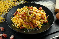 Classic Homemade Pasta carbonara Italian with Bacon, eggs, Parmesan Cheese on black plate. Royalty Free Stock Photos