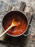 Classic homemade tomato sauce in the pan on a wooden chopping board on brown background, top view. Pasta, pizza tomato sauce. Vegetarian food Stock Images