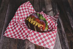 Classic hot dog with toppings on dark background. Stock Image